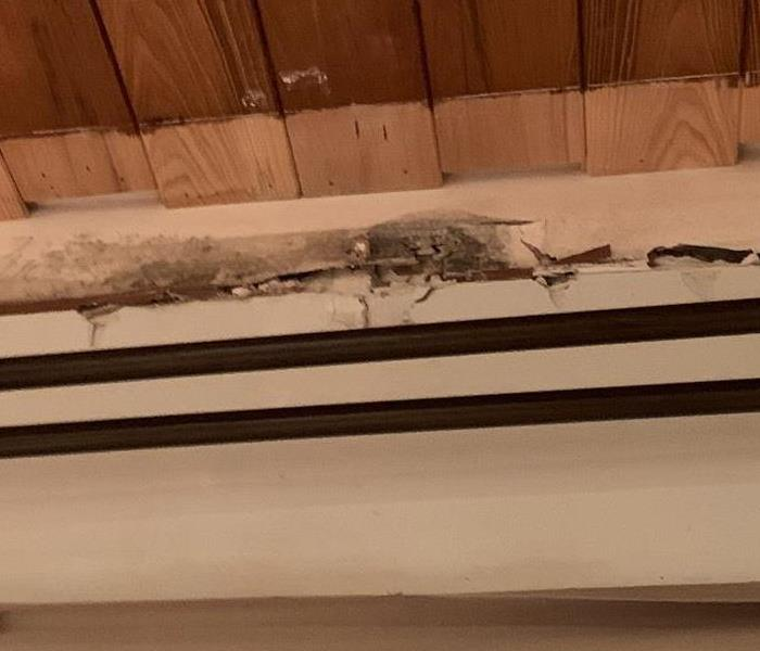 black mold on a wall above the doorway and 2 curtain rods and below the wood ceiling